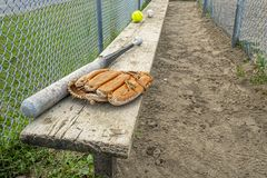 Baseball bat glove and balls on a wood bench in a park