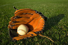 Baseball glove with baseball on the field royalty free stock photography
