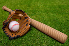 Baseball glove,bat and ball on. Baseball bat, ball and glove isolated on a field of grass Stock Photo
