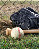 Baseball, glove, and bat in a field next to a chai Royalty Free Stock Image