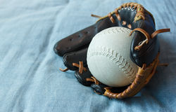 Baseball in a glove on blue bed Stock Image