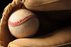Baseball and Glove Close up. Close up shot of a well worn baseball and catchers mitt horizontal format Royalty Free Stock Image