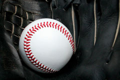 Baseball in Glove. A close up picture of a baseball inside of a black baseball glove Royalty Free Stock Photo