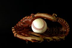 Baseball glove in the dark. Baseball glove andball on a black background Stock Photos