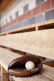 Baseball Glove in Dugout. Baseball glove and ball sit in a dugout. Shallow depth of field stock photo