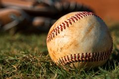 Baseball and Glove on Field. Well Worn Baseball and Glove on Field Royalty Free Stock Image