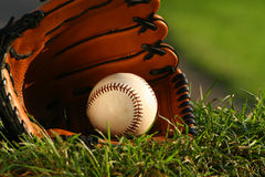 Baseball and glove on the grass after the big game. Baseball and glove on the grass stock photo