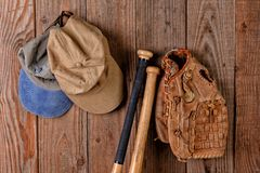 Baseball Glove and Hats hannging from a nail in a wood wall stock photos