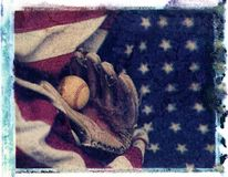 Baseball glove mit with baseball laying on red white and blue am. Erican flag showing stars Stock Images
