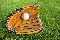 Baseball and glove in Outfield Grass. Wide angle photograph of a used baseball in a glove in the outfield grass stock images