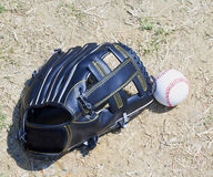 Baseball and glove over dirt Royalty Free Stock Photos