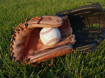 Baseball Gloves After Game. An old baseball & adult & child leather gloves in grass; one worn & one newer.  Late afternoon light.  Possible Fathers' Day image Royalty Free Stock Photography