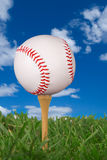 Baseball on golf tee. From the ground level with grass and cloudy sky royalty free stock images