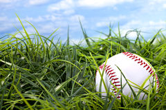 Baseball in grass with blue sky and white clouds Stock Photos
