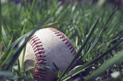 Baseball on ground with grass. Old white baseball showing seams on grass background, showing sports equipment from angle perspective.  Ball is round and shows Royalty Free Stock Photo