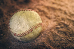 Baseball on ground. Old baseball on a ground, with shining and shadows Royalty Free Stock Image