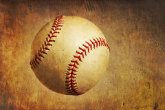 A baseball on a grunge textured background. A baseball on a golden orange grunge textured background stock photo