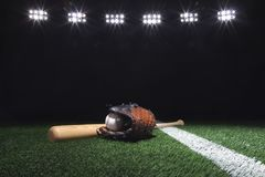 Baseball, Handschuh und Schläger auf Feld unterhalb der Lichter nachts Lizenzfreie Stockfotos