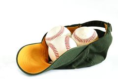 Baseball hat. Green baseball hat and three balls inside on a white background Stock Photography