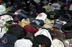 Baseball hats and roses on ground. Boston, Massachusetts USA - April 2013 - Baseball hats left as mementoes to the victims of the Boston Marathon bombing Stock Photography