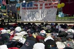 Baseball hats and roses on ground. Boston, Massachusetts USA - April 2013 - Baseball hats left as mementoes to the victims of the Boston Marathon bombing- Copley Stock Photos