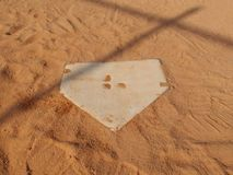 Baseball home plate. From the catcher's point of view. The base sits in red sand and has a shadow of a fence over it royalty free stock photo