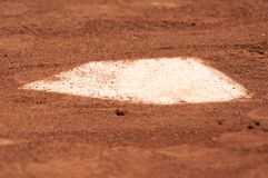 A baseball home plate is surrounded by dirt. And shallow depth of field Royalty Free Stock Photo