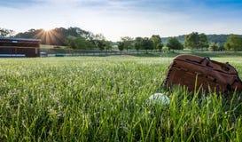 Baseball i r?kawiczka na trawie w ranek rosie blisko schron wczesnej wiosny fotografia royalty free