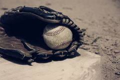 Baseball laying in glove on field, vintage style. stock photos