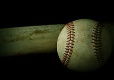 Baseball. Low key image of old baseball and bat showing pine tar residue on black background. Vintage filter applied stock photo