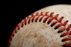 Baseball macro over black. Macro of a baseball over black, shallow depth of field with focus on set of stitches Royalty Free Stock Photos