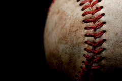 Baseball macro over black. An abstract macro of a used baseball with focus on a set of stitches, shot over black Royalty Free Stock Images