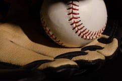 Baseball med handsken på svart bakgrund Arkivbild