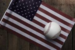 Baseball mit amerikanischer Flagge im Hintergrund Lizenzfreie Stockfotografie