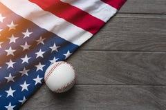 Baseball mit amerikanischer Flagge im Hintergrund Stockfotos