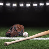 Baseball mitt ball and bat at night under stadium lights. On grass field with white stripe Royalty Free Stock Photos
