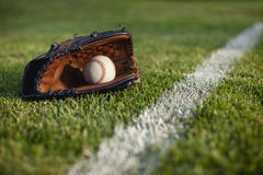 Baseball mitt and ball on field with white line. A selective focus on baseball mitt and ball sitting near a white line on a baseball field stock photography