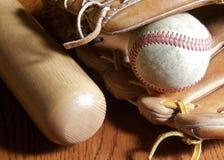 Baseball, mitt and bat. Baseball glove, ball and bat sitting on a wood surface Stock Photo