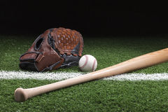 Baseball with mitt and bat on green grass at night Royalty Free Stock Photo
