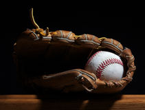 Baseball and mitt on a bench. A baseball sits in a mitt on a wood bench set against a dark background Stock Images