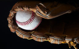 Baseball in mitt on black. A baseball sits in a mitt set against a dark background Royalty Free Stock Photography