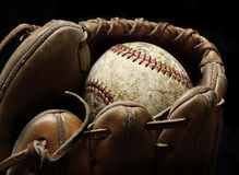Baseball and Mitt or Glove. Worn old baseball in brown leather mitt or glove Royalty Free Stock Image