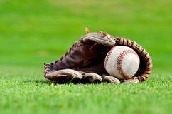 Baseball in mitt on green grass royalty free stock photo