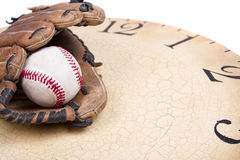 A baseball and mitt on an old vintage clock Stock Image