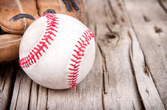 Baseball and mitt on wooden background. Close-up of baseball and mitt on rustic wooden background Stock Photos