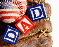 Baseball with mitt and the word Dad. All American dad - wooden blocks in a baseball glove with an American flag wrapped baseball - concept for Father's Day Stock Photo