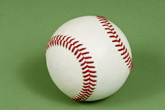Baseball on Mottled Green Background. A baseball hardball with red stitching on a green background Royalty Free Stock Images