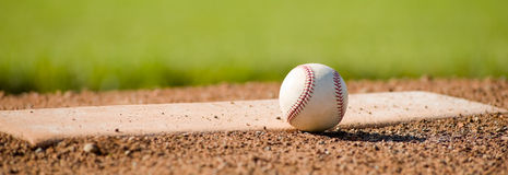 Baseball on Mound. A white leather baseball lying on top of the pitcher's mound at a baseball field with copy space Royalty Free Stock Images