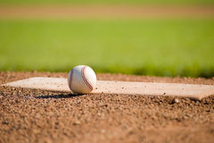 Baseball on Mound. A white leather baseball lying on top of the pitcher's mound at a baseball field with copy space Stock Photos