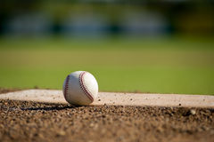 Baseball on Mound. A white leather baseball lying on top of the pitcher's mound at a baseball field with copy space